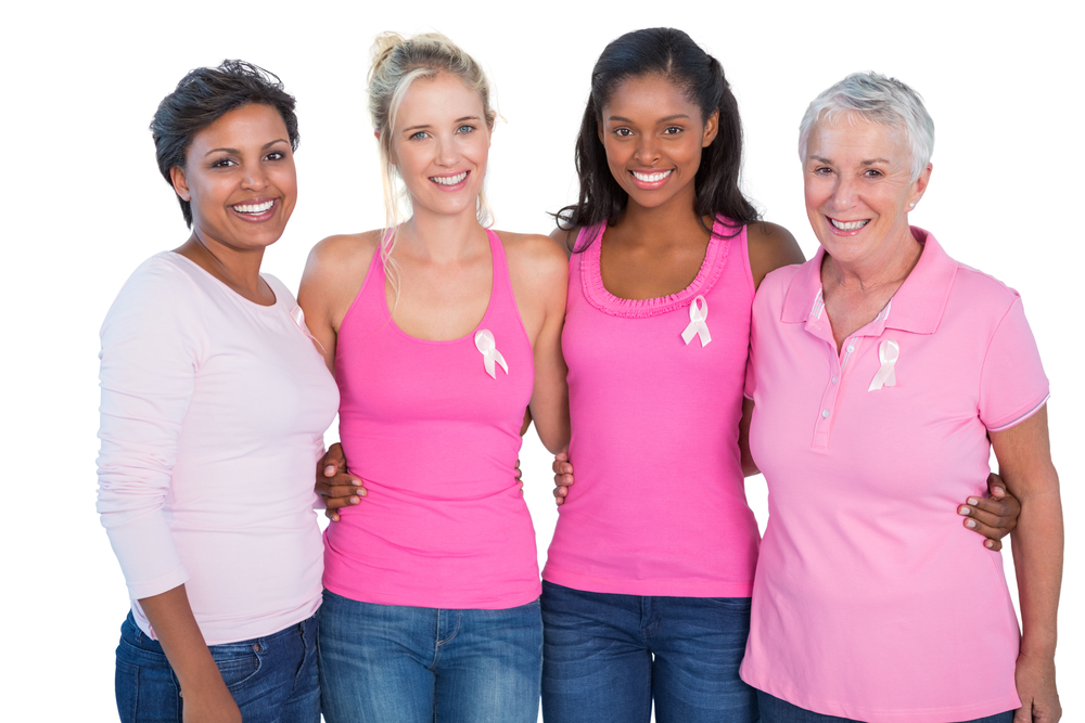 Smiling women wearing pink tops and breast cancer ribbons on white background