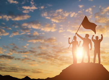 Silhouette of victory team on mountain with sunset and sky background